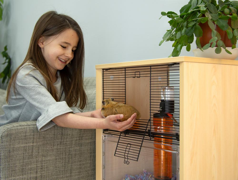 En smilende jente tar ut hamsteren sin fra hamsterburet Qute.