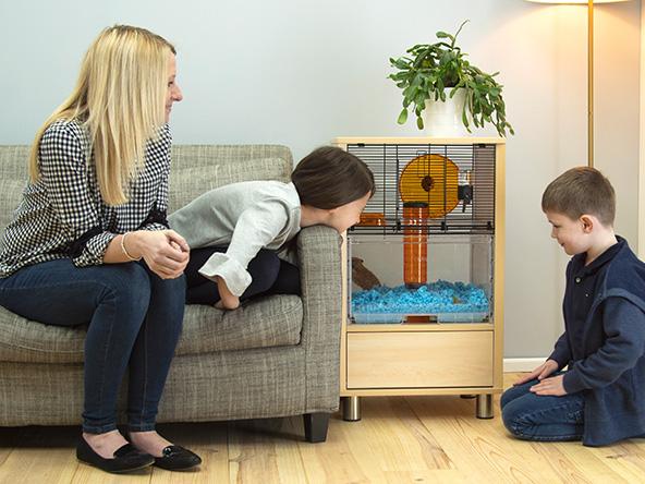 En kvinne som sitter på sofaen smilende mens barna hennes studerer hamsteren i hamsterburet sitt.
