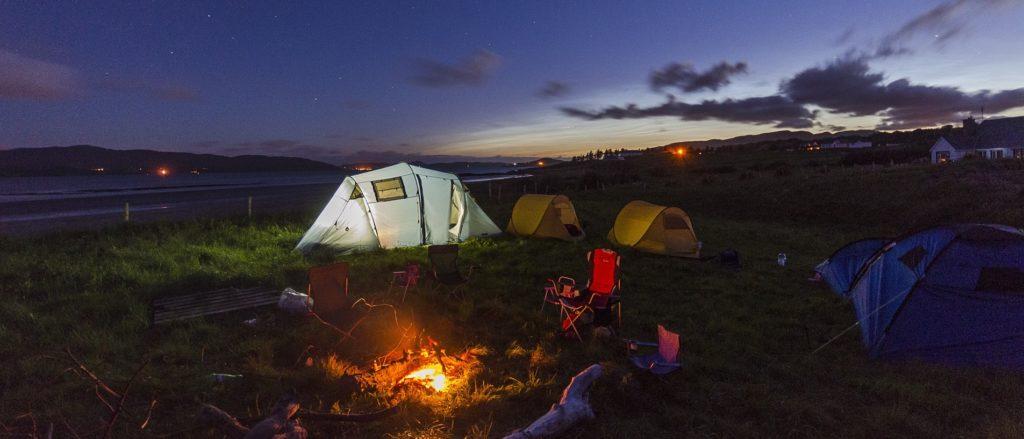 Oppslådde telt rundt et bål like før det begynner å bli helt mørkt.