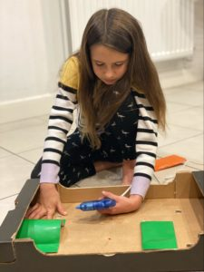 En jente som sitter på gulvet og limer forskjellige deler til hinderløypen sin.