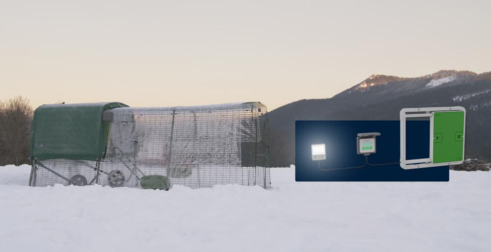 Sammenkoblingen mellom autodøren, kontrollpanelet og hønsehuslyset, med et Eglu hønsehus og -luftegård dekket av snø i bakgrunnen.