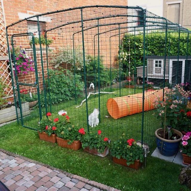 Denne luftegården har blomsterkasser og planter plassert på utsiden, noe som gjør at luftegården blender inn og blir en del av hagen.