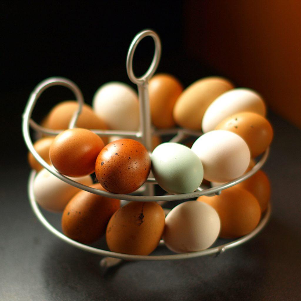 Egg i forskjellige farger - oransje, gyldenbrune, hvite - på et eggestativ formet som en spiral.