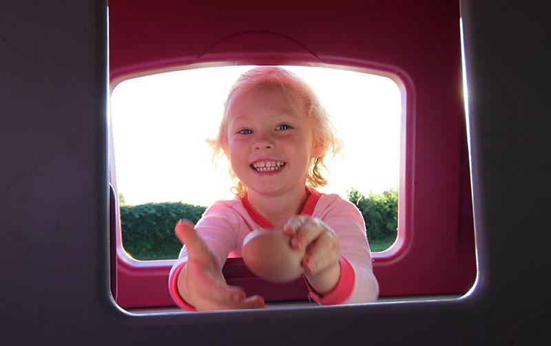 Et smilende barn med blondt hår som titter inn i eggluken på Eglu Cube for å se etter nylagte egg til frokosten.