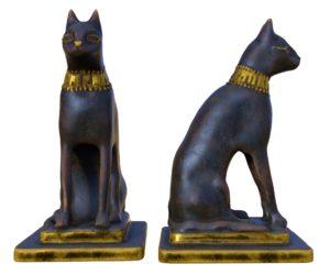 Bilde av en gull og svartmalt statue av en sittende katt sett forfra og fra siden.