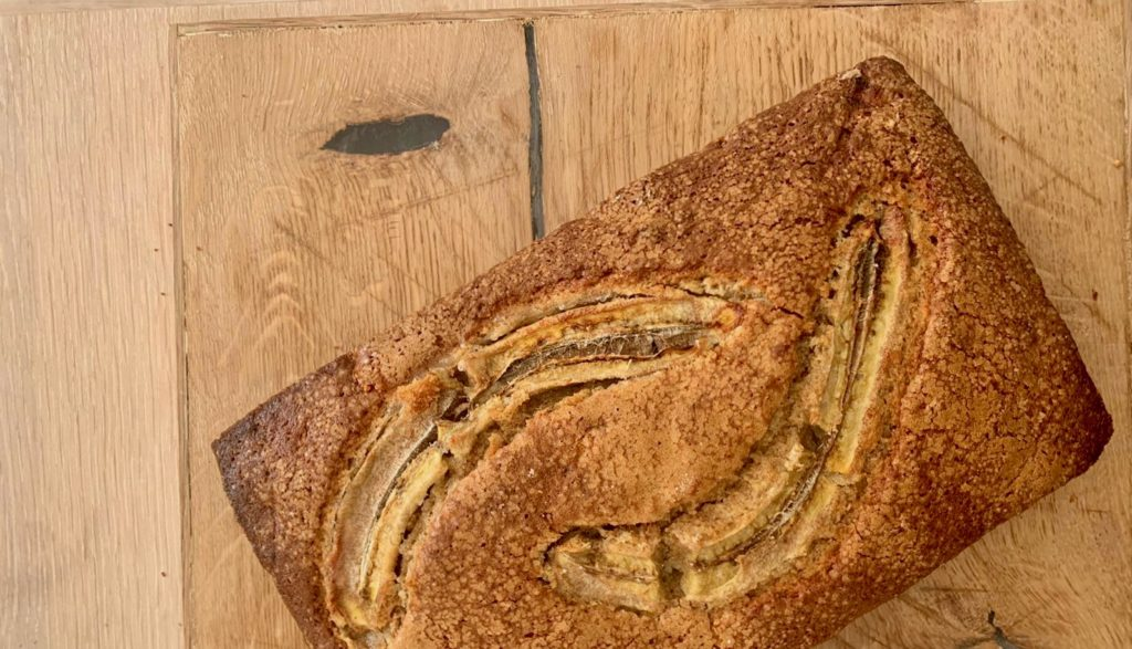 Et nybakt bananbrød, dekorert med en splittet banan som ligger på en trefjøl på kjøkkenbenken.
