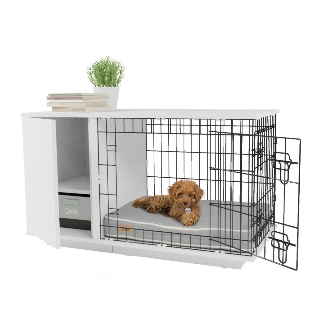 En liten hund med brun, krøllete pels og halsbånd ligger inni sitt Fido Studio hundebur fra Omlet.