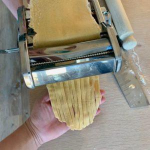 Hjemmelaget pasta: en hånd tar imot tagliatelle-pastaen som kommer ut av pastamaskinen. Nå trenger den bare å tørke, så kan den kokes eller fryses til når du selv måtte ønske å spise den!