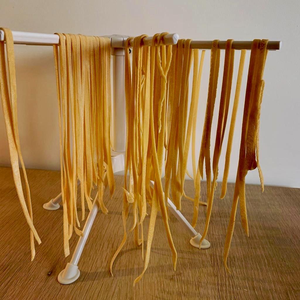 Et stativ med mange strimler av fersk pasta hengende på hver arm.